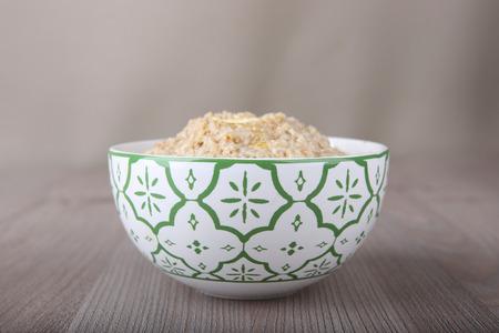 Oatmeal porridge in bowl on wooden table