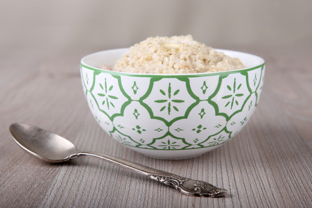 Oatmeal porridge in bowl with spoon on wooden table