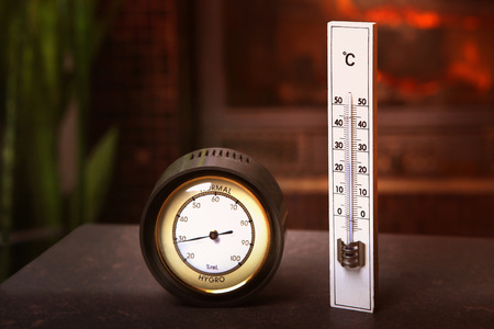 humidity gauge: Hydrometer and thermometer in front of fireplace