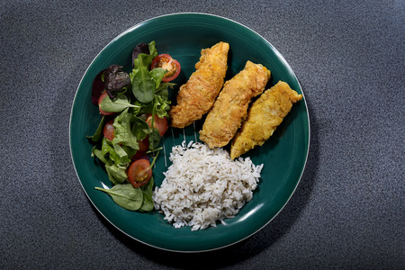 Plate with chicken fried, rice, salad from above Stock Photo