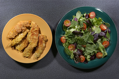 Breaded chicken fillets and salad