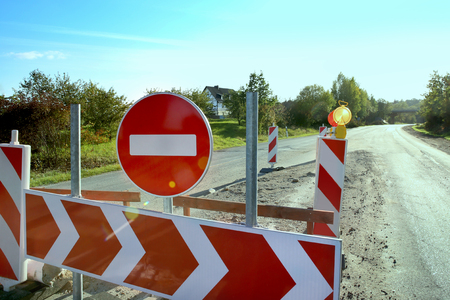 deviation: No entry traffic sign on road. Prohibiting sign, white arrow on red sharp deviation of route sign. Stock Photo