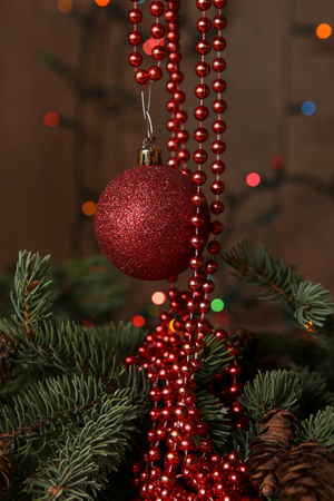 Red bauble and beaded garlands decor. Christmas card. Decoration on chirstmas tree. Stock Photo