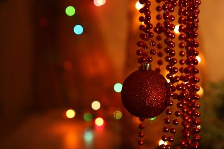 赤い安物の宝石とビーズの花輪の装飾。赤とオレンジ党のボケ味。クリスマスの背景を抽象化します。