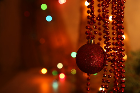 Red bauble and beaded garlands decor. Red and orange party bokeh. Abstract Christmas background. Stock Photo