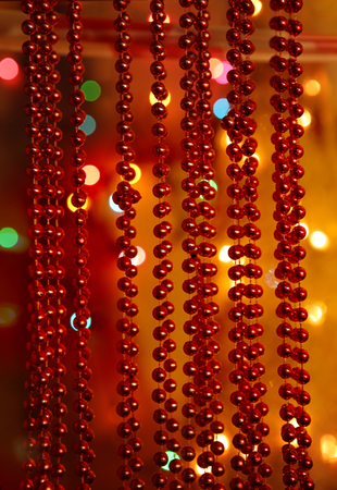 Beaded garlands decor.  Red and orange christmas bokeh above firtree.  Abstract Christmas background. Stock Photo