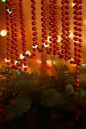 Beaded garlands decor. Red and orange christmas bokeh above firtree.  Abstract Christmas background.