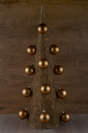 Decorative Christmas tree made from straw  with golden balls isolated on wooden background Stock Photo