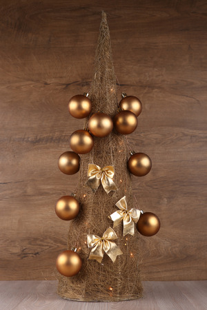 Decorative Christmas tree made from straw  with golden balls and bows isolated on wooden background