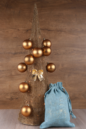 Decorative Christmas tree made from straw  with golden balls and blue jute gifts Santa bag on wooden background Stock Photo