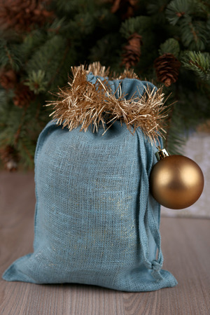 Soft blue Santa bag in Christmas time. Woven linen fabric pouch. Gifts bag decorated with gold ball.