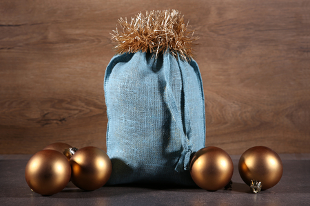 Soft blue Santa bag and  golden balls. Woven linen fabric pouch. Gifts bag in wooden background.