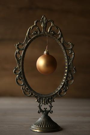 Vintage mirror frame and christmas ball. Subtle Christmas mood.