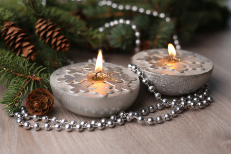 Silver Christmas candles decorated with snowflakes near christmas tree, garlands. Stock Photo