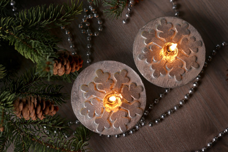 Silver Christmas candles decorated with snowflakes near christmas tree, garlands. Top view.