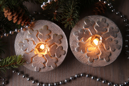Silver Christmas candles decorated with snowflakes near christmas tree, garlands. Top view. Candlelight. Stock Photo