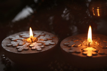 Silver Christmas candles decorated with snowflakes near christmas tree, garlands. Candlelight.