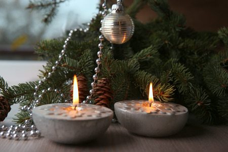 Christmas decoration. Silver Christmas candles decorated with snowflakes near christmas tree, garlands.