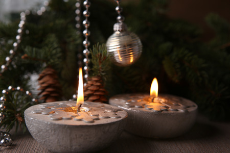 Christmas decoration. Silver Christmas candles decorated with snowflakes near christmas tree, garlands.  Candlelight. Stock Photo