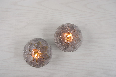 Silver  candles  with snowflakes. Winter, Christmas decoration on wooden white background.
