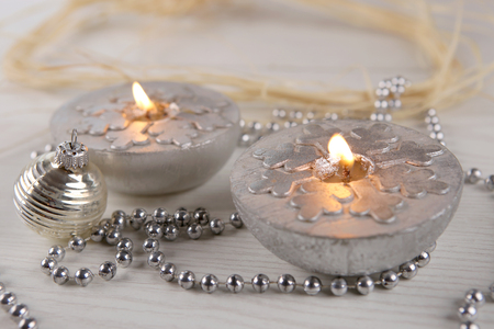 Silver  candles  with snowflakes.  Winter, Christmas decoration on wooden  background.
