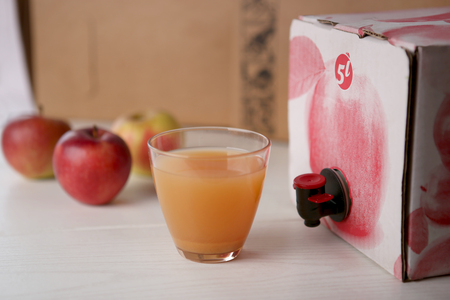 Apple juice  in glass. Homemade apple juice from box.