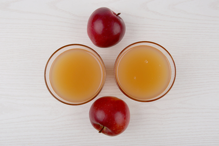 Two red apples and two glasses of juice on white wooden background. Top view. Stock Photo