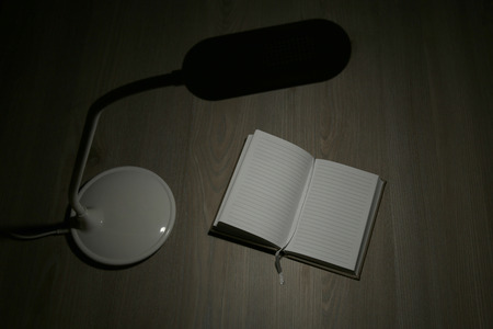 Table lamp and open notebook on wooden desk.  Top view. Stock Photo