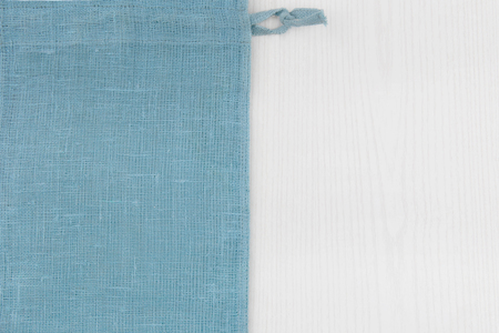 Sack from left sidewhite  wooden table. Soft blue woven linen fabric texture  wood texture. Coarse jute sack.  Top view background.