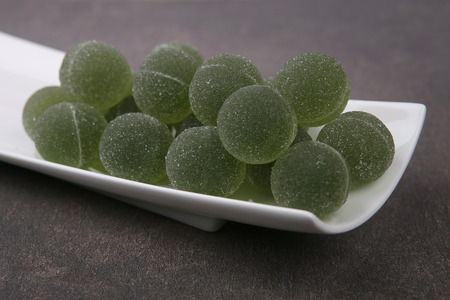 Sweet jelly flavor fruit green dessert. Round candies in plate. Stock Photo