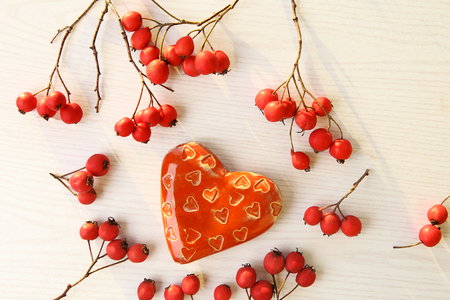 Ceramic heart and hawthorn berries on white wooden background. Top view.