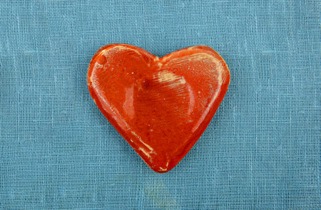 ceramic heart: Ceramic heart top view. Decorative heart on blue woven linen background. Stock Photo