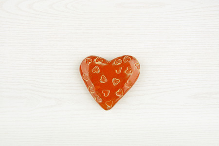 ceramic heart: Ceramic heart isolated on white wooden background. Decorative red heart top view.