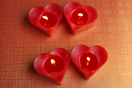 Heart shape candles. Four red candles burning. Stock Photo