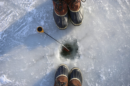 Ice fishing on frozen lake. Two people  fishing together. Ice hole, winter rod and boots. Stock Photo