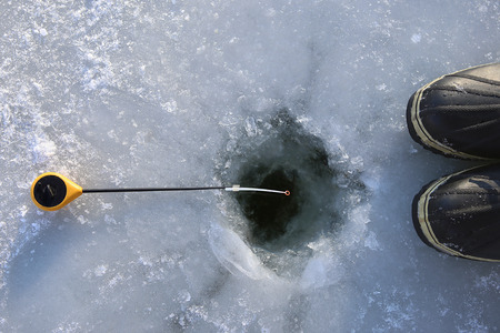 Ice fishing on frozen lake.  Ice hole, winter rod and boots..