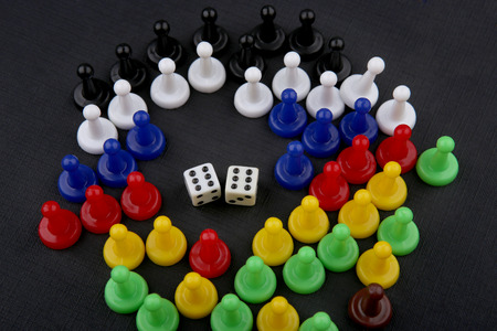 Colorful play figures and dices with double six. Board game pieces and dices on black background.