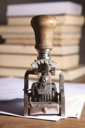 Vintage date stamp. Industrial office stamp. Old numbering machine on table with documents and books.