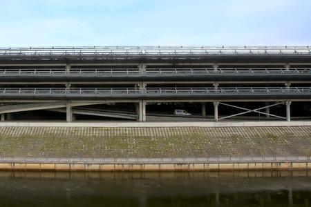 multi story car park: Multi Storey Parking Lot. Industrial building car parking garage near river. Stock Photo