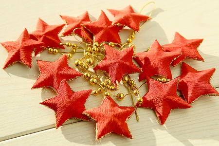 estrellas cinco puntas: Red five-pointed stars garland. Decoration with stars on white wooden surface.