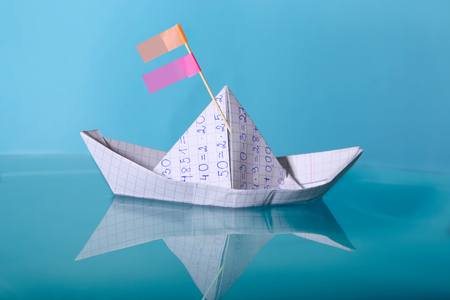 Paper boat made from mathematics notebook paper. Origami paper ship sailing on blue water surface.