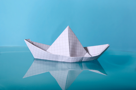 Paper boat made from notebook paper. Origami paper ship sailing on blue water surface. Stock Photo
