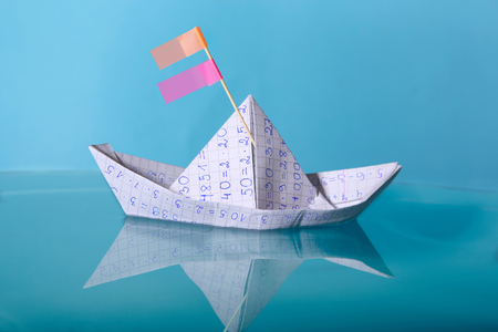 Paper boat made from mathematics notebook paper. Concept of creativity in education. Origami paper ship sailing on blue water surface.