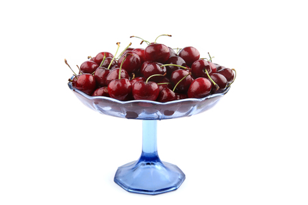 Cherries in glass stand isolated on white background. Fruits cherries in bue glass bowl.