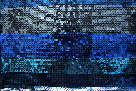 Abstract blue spangles background. Fabric texture with bright blue  circles beads or sequins.