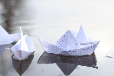 Naves de papel origami navegando en el río. Barcos de papel hechos de papel de cuaderno de matemáticas. Foto de archivo - 89543718
