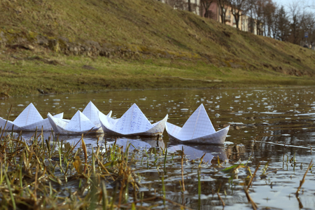 Origami paper ships sailing in river. Paper boats made from mathematics notebook paper.