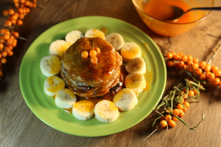 A stack of homemade vegan pancakes with banana and sea buckthorn jam. Pancakes made with linseed, flour and banana.