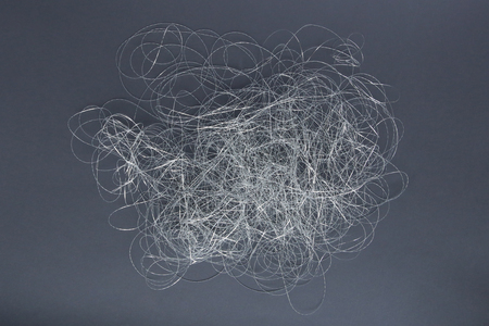 Silver thread pile like cloud. Pile of silver thread on grey background. Stock Photo