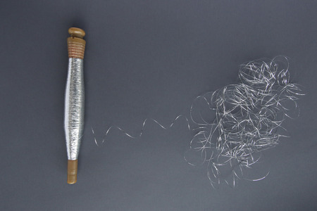 Silver thread pile like cloud and spool of silver thread. Reel or spool of silver thread on grey background. Stock Photo